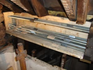 Beam splice with steel connecting rods encased in a retained shutter to be filled with epoxy resin structural grout